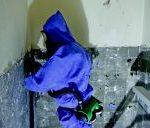 Das Foto zeigt einen Handwerker beim Schleifen eines asbesthaltigen Fliesenklebers